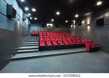 Interior of a small theater with red chairs.