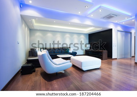 Interior of a spacious luxury living room with colorful ceiling lights - stock photo