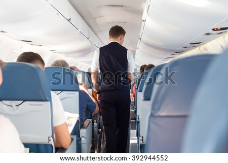 Interior of airplane with passengers on seats and steward walking the aisle.  - stock photo