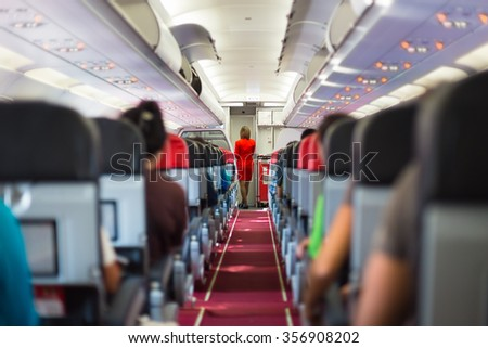 Interior of airplane with passengers on seats and stewardess in red uniform at the aisle.