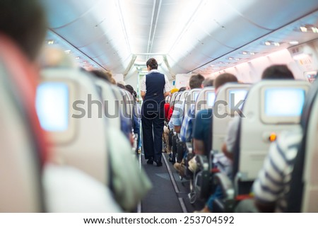 Interior of airplane with passengers on seats and stewardess in uniform walking the aisle.  - stock photo