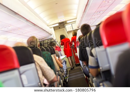 Interior of airplane with passengers on seats and stewardess walking the aisle. - stock photo