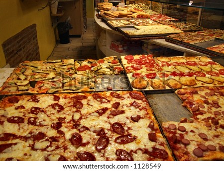 interior of an italian pizzeria kitchen room with many delicious pizzas with different ingredients. Interior Design Ideas. Home Design Ideas