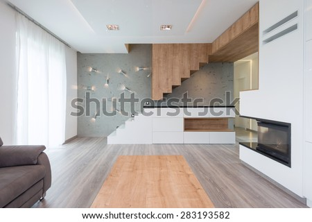 interior of beautiful modern living room with stairway and fireplace - stock photo