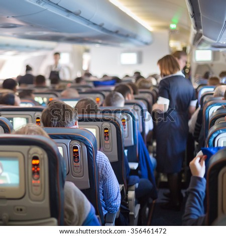 Interior of big commercial airplane with passengers on seats during flight. Stewardess in blue uniform walking the aisle, serving meal to people. Square composition. - stock photo