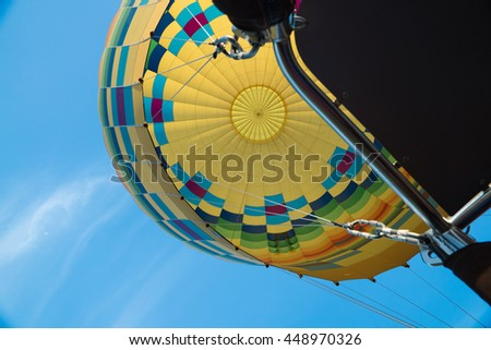 Interior of bright yellow hot air balloon against blue sky - stock photo