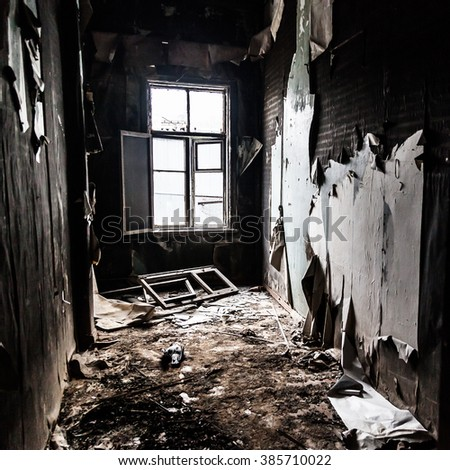 interior of burned house with white window and lots of garbage on the floor   - stock photo