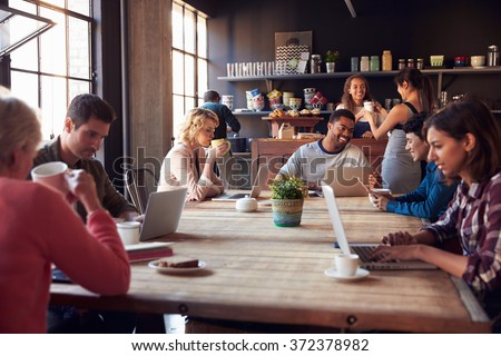 Interior Of Coffee Shop With Customers Using Digital Devices - stock photo