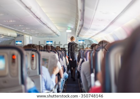 Interior of commercial airplane with passengers on seats during flight. Stewardess in dark blue uniform walking the aisle. Horizontal composition. - stock photo
