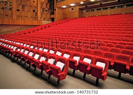 Interior of empty auditorium with red arm-chairs