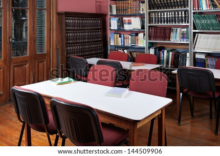 Interior of empty library with bookshelves and seating arrangement - stock photo