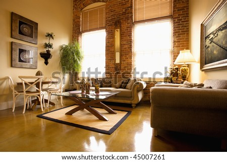 Interior of furnished living room with large windows and brick wall. Horizontal shot. - stock photo