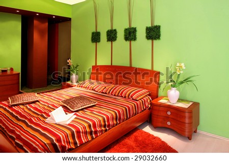 Interior of green bedroom with big bed