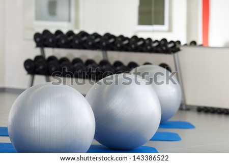 Interior of gym with fitness balls in a row - stock photo