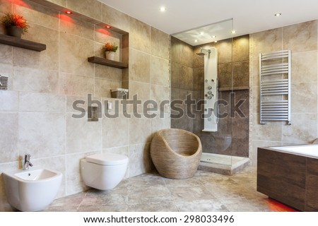 Interior of luxury bathroom with beige tiles - stock photo