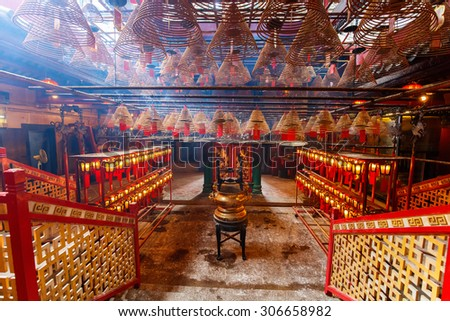 Interior of Man Mo Temple in Hong Kong with incense offerings and coils suspended from the ceiling - stock photo