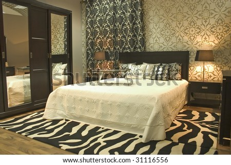 Interior of modern bedroom. Cosy walls with graphical elements. Mirrors and zebra carpet. - stock photo