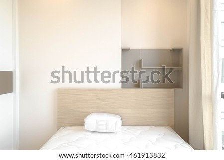 Interior of Modern Bedroom in white and beige (soft earth tone) new condition for newly move-in. Living in apartment concept. Selective focus on the wooden headboard. Window Light.