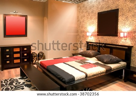 Interior of modern bedroom with furniture floral wallpapers and hot colors. - stock photo