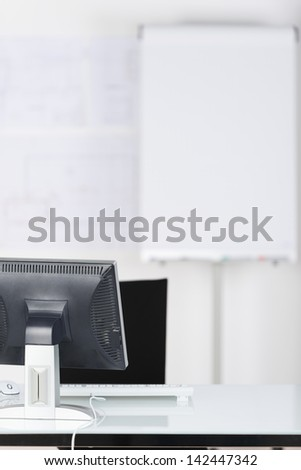 Interior of office with computer and flipchart - stock photo