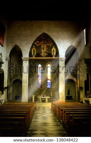 Interior of old church in Dominican monastery in Dubrovnik, dark interior with rays of light shining through the window - stock photo
