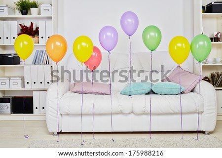 Interior of room with big soft white sofa, light carpet on  floor and row balloons hanging in air - stock photo
