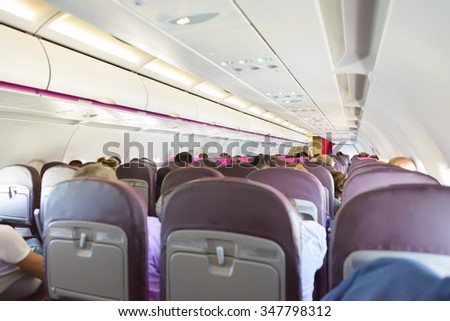 Interior of the passenger airplane with passengers on seats - stock photo