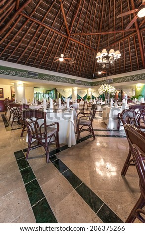 Interior of the tropical, caribbean restaurant with nicely served and decorated tables of the luxury resort. Vertical. - stock photo