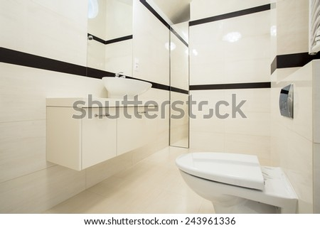 Interior of toilet with beige and black tiles - stock photo