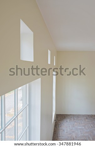 Interior of unfinished living room with tile wooden floors and big windows - stock photo