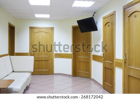 Interior of waiting area with five doors and a white sofa in the medical center hospitals - stock photo
