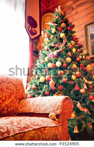 Interior of wooden chalet with christmas tree and sofa