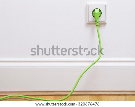 Interior outlet with a green plugged in cable - stock photo