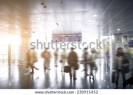 Interior photo of blurred passengers looking at airport schedule at sunny day - stock photo