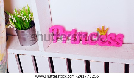 Interior photo of home decor for little princess with pink wooden word is on the shelf of the cupboard near the bouquet of may lily - stock photo