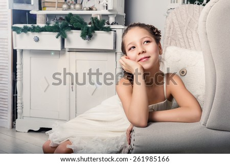 Interior portrait of a cute little girl sitting in a living room - stock photo
