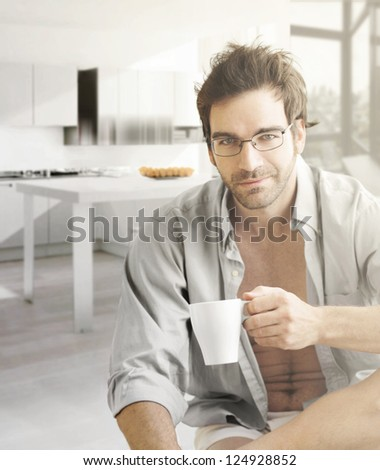 Interior portrait of a hot looking relaxed happy male model with a cup of morning coffee - stock photo