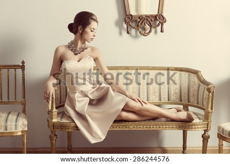 interior portrait of brunette elegant girl lying on retro sofa in aristocratic room. Wearing pink dress, precious jewellery and classic hair-style. Luxury atmosphere  - stock photo