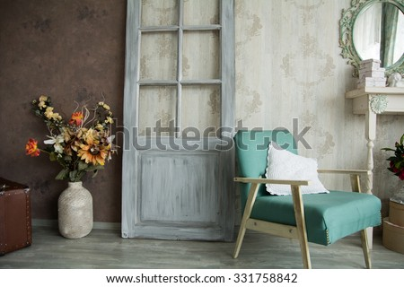 Interior retro room with an armchair, flowers, door and mirror.