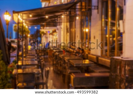 Interior small restaurant blurred background. Blurred bokeh cafe interior in warm dark colors. As background for creative fashion design. Restaurant, coffee shop with a beautiful background blur bokeh