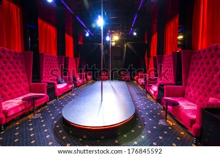 interior strip club with sofas and tables poles - stock photo