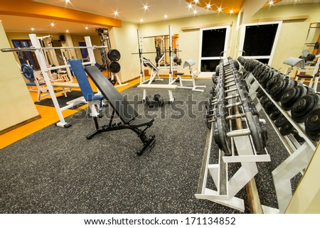 Interior view of a gym with equipment and weights. - stock photo