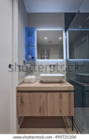 Interior View Of A Modern Bathroom In Foreground The Counter Top Washbasin And Wood Furniture