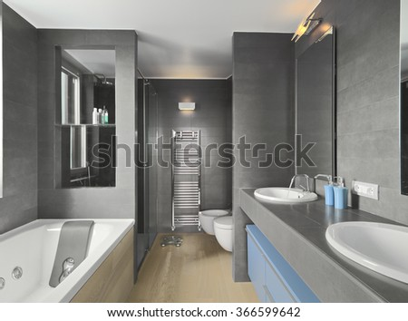 interior view of a modern bathroom in foreground the washbasin and the bathtub - stock photo