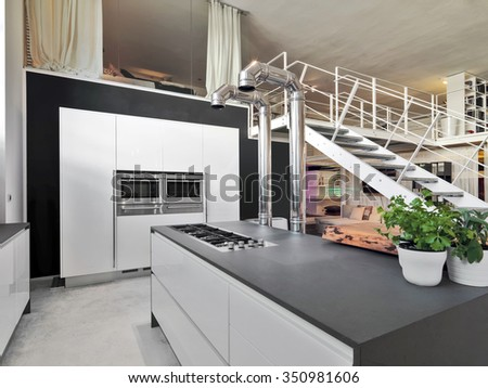 interior view of a modern kitchen in the loft with iron staircase - stock photo