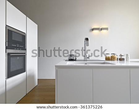 interior view of a modern kitchen with kitchen island, sink and oven the floor is made of wood  - stock photo
