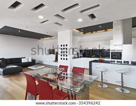 interior view of apartment with wood floor in foreground the glass dining table overlooking on the modern kitchen and on living room with leather sofa - stock photo