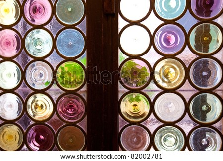 Interior view through a stained glass window, consisting of many circular colored glass pieces each encased in iron rings and wooden window frame