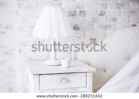 Interior. White lamp and  cup of coffee on a bedside table in a bedroom in early  morning. - stock photo