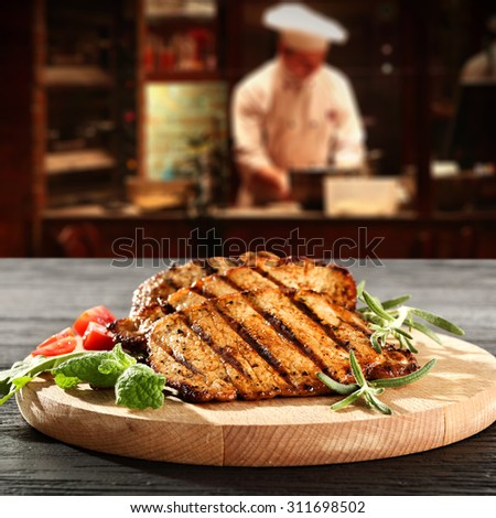 interior with cook of restaurant kitchen and steak on wooden desk top  - stock photo